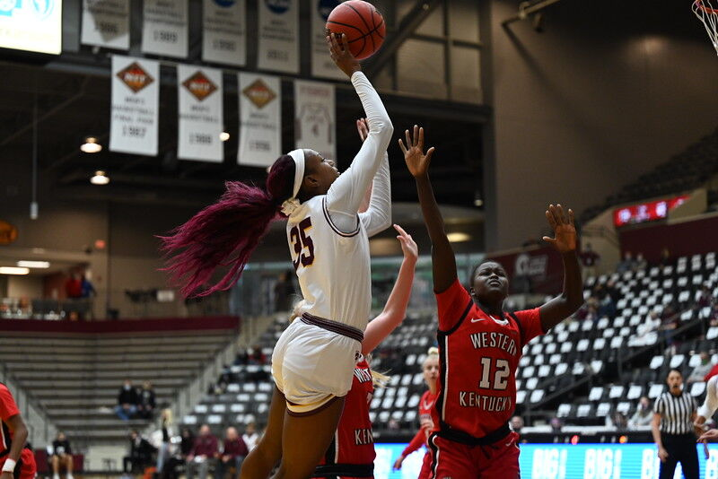 Senior+forward+Teal+Battle+%2835%29+attempting+a+jump+shot+over+Lady+Topper+senior+forward+Fatou+Pouye+%2812%29.+The+Lady+Trojans+defeated+WKU+63-47+on+Dec.+13%2C+2020.%C2%A0