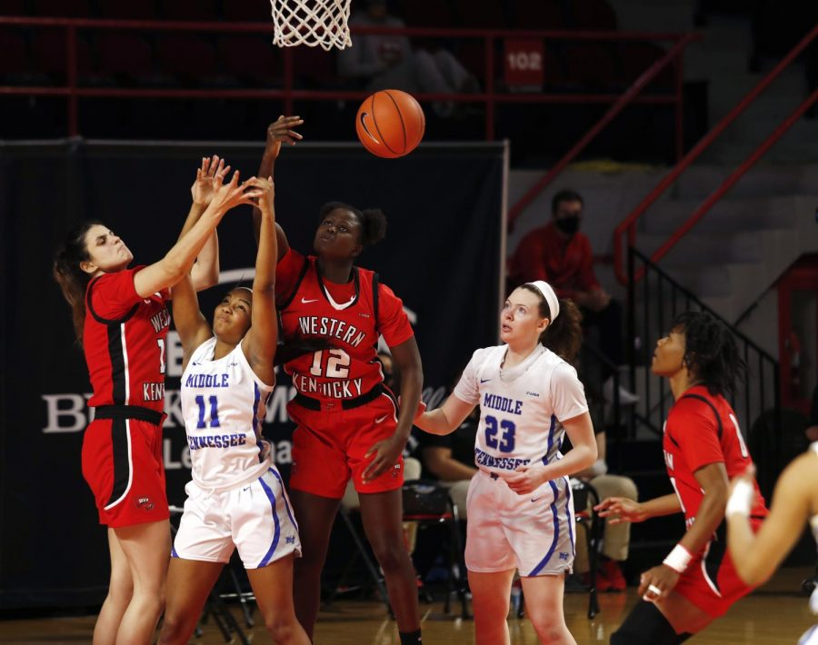 Western Kentucky University senior forward Fatou Pouye (12) and senior forward Raneem Elgedawy (15) rebound the ball during Saturday nights game against the Middle Tennessee State University. The WKU Lady Hilltoppers fell to the MTSU Blue Raiders 77-60.