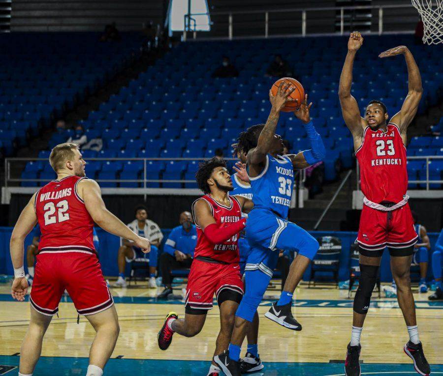 (Middle) Freshman Dayvion McKnight (20) attempting to defend MTSU's junior Dontrell Shuler (33). WKU junior big man Charles Bassey (23) reaches for the block against the Blue Raider guard on Jan. 24, 2021.