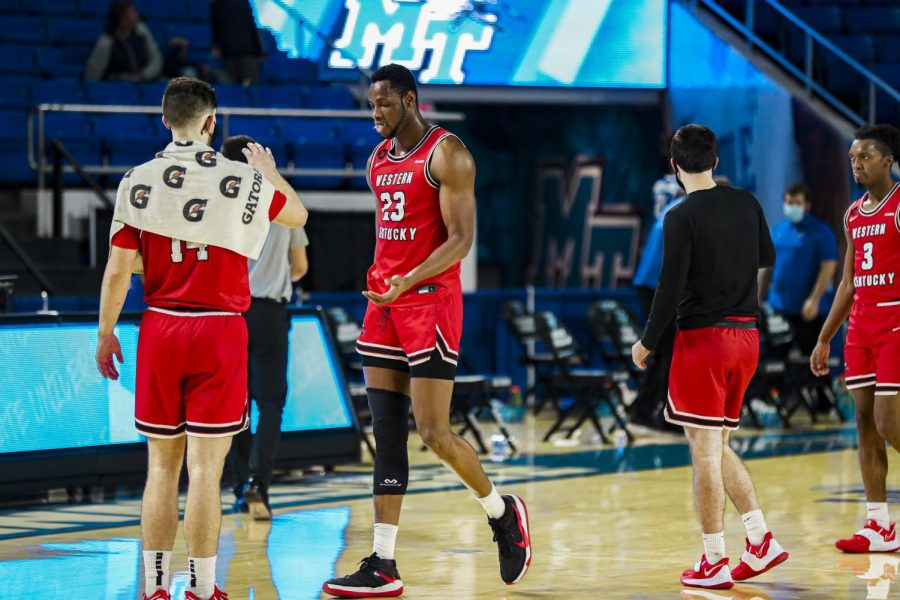 WKU junior Charles Bassey (23) being greeted by teammate Luke Frampton on the sideline. The Hilltoppers took down Middle Tennessee 68-52 on Jan. 24, 2021.
