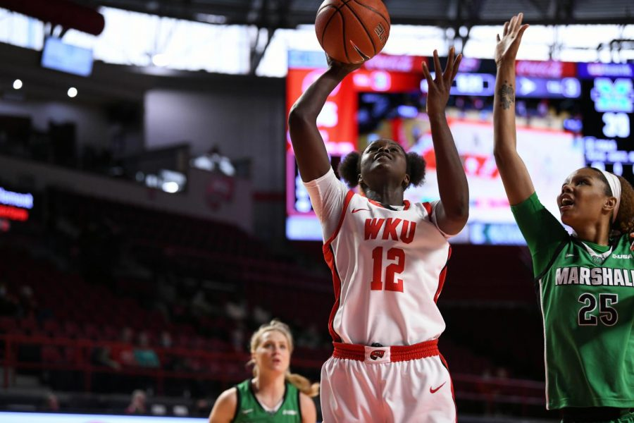 Lady Topper senior Fatou Pouye (12) attempting a shot over Marshall redshirt sophomore Mahogany Matthews (25) on Jan. 17, 2021 in Diddle Arena.