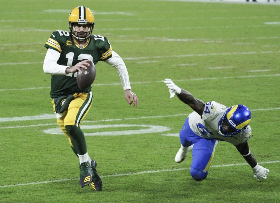 Green Bay Packers quarterback Aaron Rodgers (12) scrambles past Los Angeles Rams outside linebacker Leonard Floyd (54) for a 1-yard touchdown run in the 2nd quarter. The Green Bay Packers hosted the Los Angeles Rams in the NFC playoff game Saturday, Jan.16, 2021 at Lambeau Field in Green Bay.
