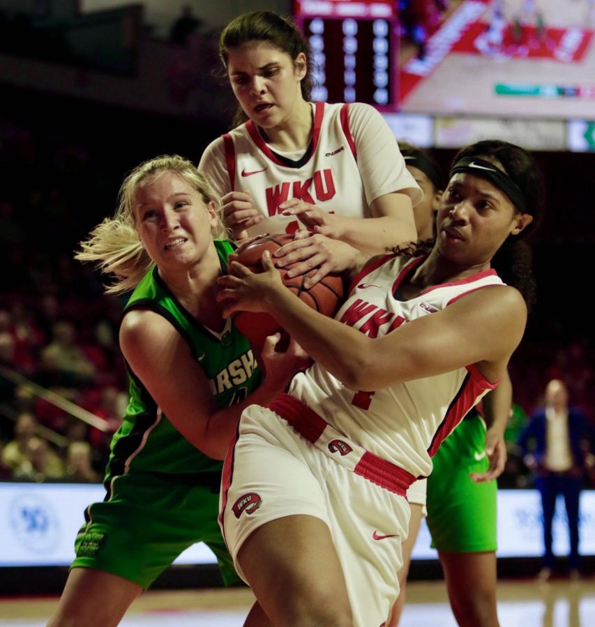Marshall freshman guard Savannah Wheeler (left), WKU junior forward Raneem Elgedawy (top) and WKU redshirt senior forward Dee Givens (right) battle for possession during the women's basketball game against Marshall on Thursday, Feb. 20. The Lady Toppers defeated the Thundering Herd 79-65.