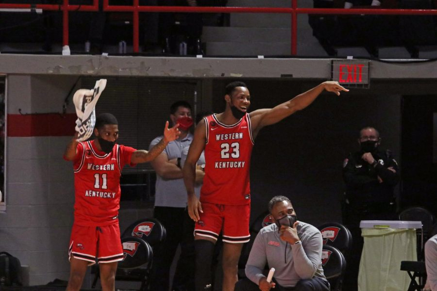 WKU teammates Taveion Hollingsworth (11) and Charles Bassey (23) cheer from the sidelines during the game against the Rice Owls on Feb. 13, 2021 in Diddle Arena.