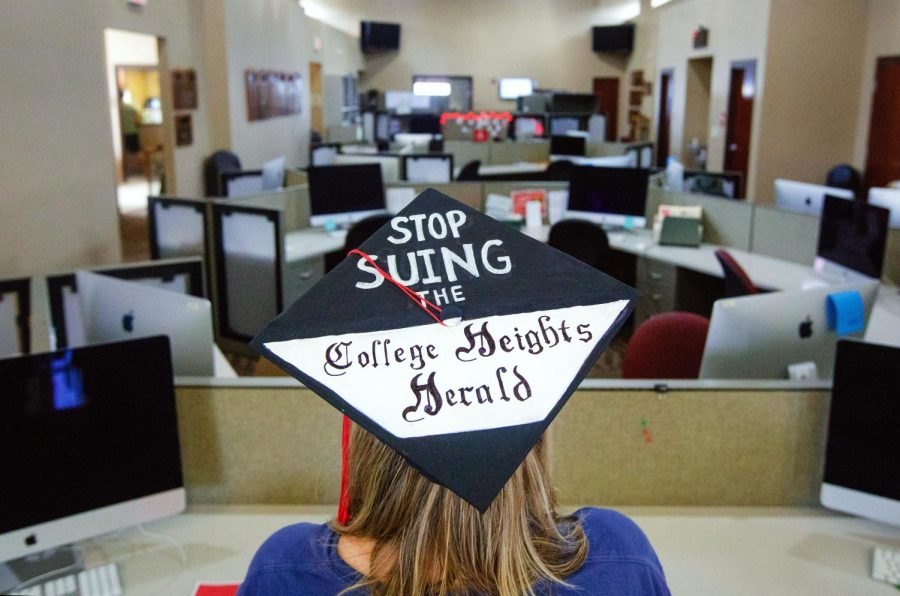 A student shows off their graduation cap art in the Adams-Whitaker Student Publication Center located on Western Kentucky University's campus on May 10, 2019.