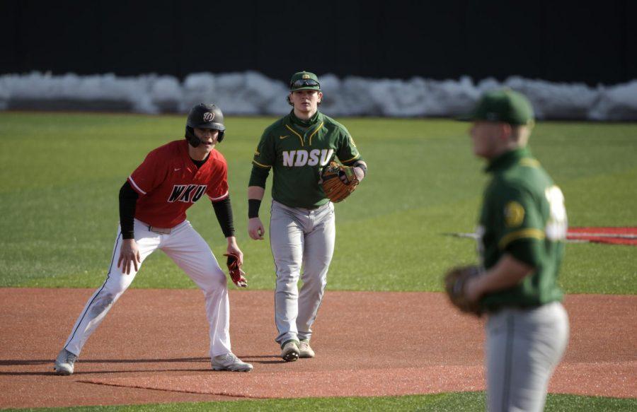 Outfielder Jackson Swiney (6) waits to run to third base as North Dakota right-hander Gabe Pilla (1) and first baseman Bennett Hostetler (1) try to hold him off.