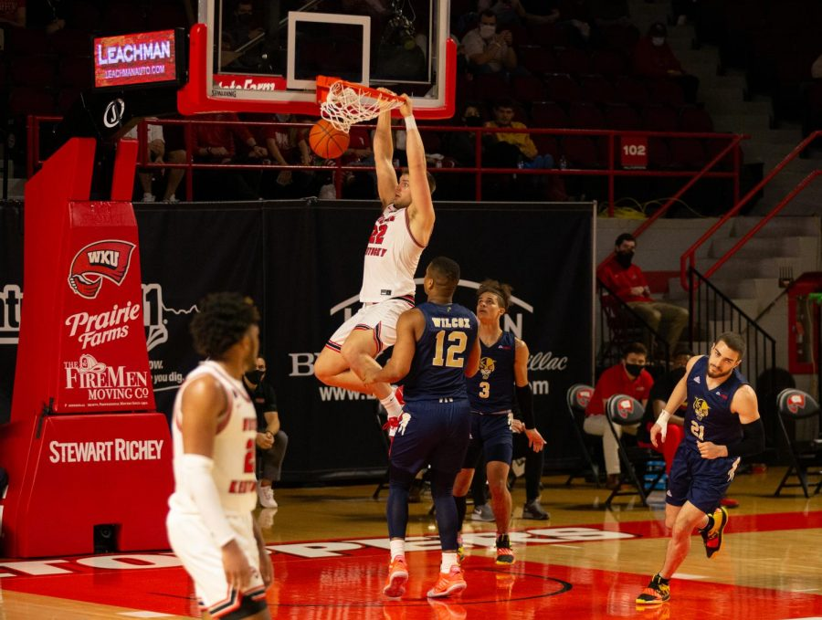Redshirt senior Carson Williams (22) slams the ball home over FIU Panther defender Dante Wilcox (12) as the Hilltoppers went on to win 91-58. Williams would go on to finish the contest with 21 points during the game on Feb. 28, 2021.