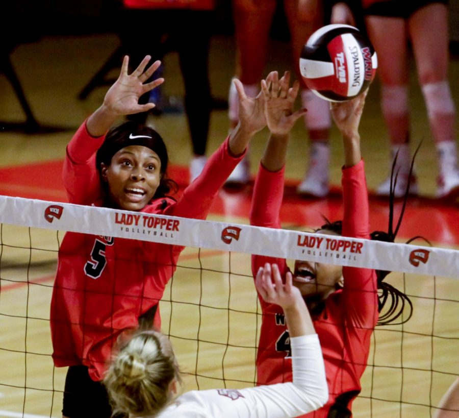WKU middle hitters Lauren Matthews (5) and Avri Davis (4) block the volleyball after a hit over the net from Bellarmine opposite side hitter Ashley Price (4) at the game on Jan. 24, 2021. WKU won all three sets.