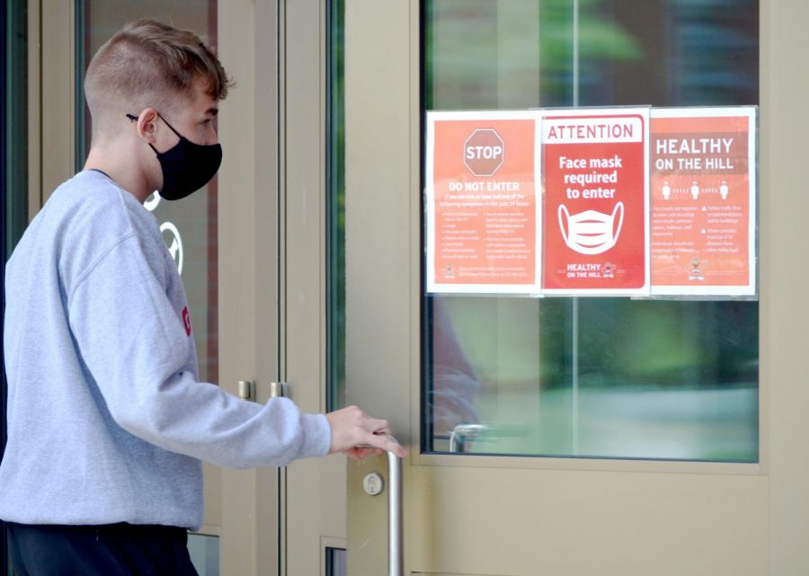 A WKU student enters the Downing Student Union on Aug. 22, 2020. Buildings across WKU's campus have signs stating that masks are required in order to enter.