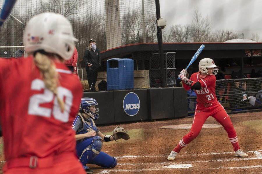 WKU+outfielder+Maggie+Trgo+%2820%29+warms+up+at+the+ondeck+circle+while+Kennedy+Foote+%2821%29+is+at+bat+against+Indiana+state+university.+The+hilltoppers+defeated+the+sycamores+6-0+in+the+hilltopper+classic+to+get+their+first+at+home+victory+on+Feb+27%2C+2021.