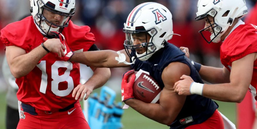 Running back Jalen John shoves his way through Nick Moore, left, and Cameron Fietz during a ball protection drill on the first day of spring practice for the University of Arizona, Tucson, Ariz., March 23, 2021.