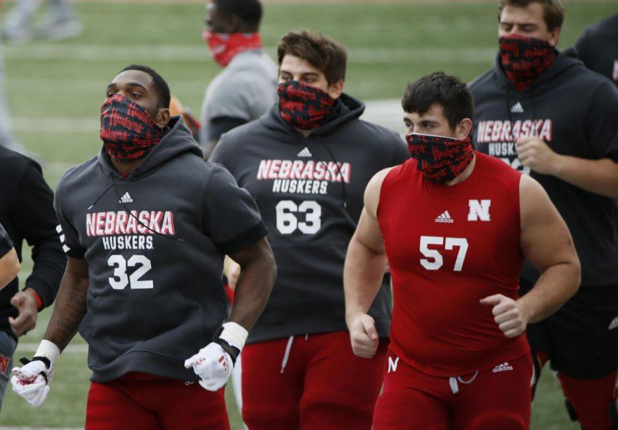 Nebraska's Niko Cooper (32), Nouredin Nouili (63) and Ethan Piper (57) take part in pregame warmups before last season's game against Ohio State in Columbus, Ohio.