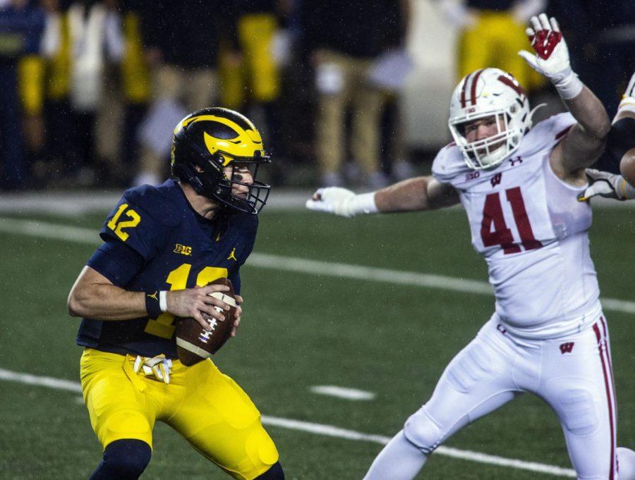 UW outside linebacker Noah Burks pressures Michigan quarterback Cade McNamara in November.