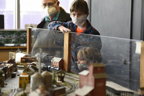 Brothers Ephraim (center) and Anselm Krans watch as a model train drives past them at the Historic RailPark and Train Museum in Bowling Green. The museum hosted a model train show on Saturday, March 6, 2021.