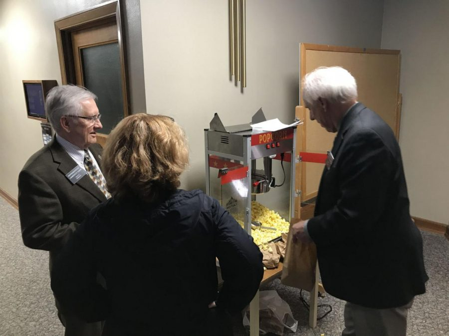 Reps. Lawrence Klemin, R-Bismarck, Mary Johnson, R-Fargo, and Dennis Johnson, R-Devils Lake, help themselves to popcorn from a machine that triggered two fire alarm evacuations of the state Capitols legislative wing on Monday.