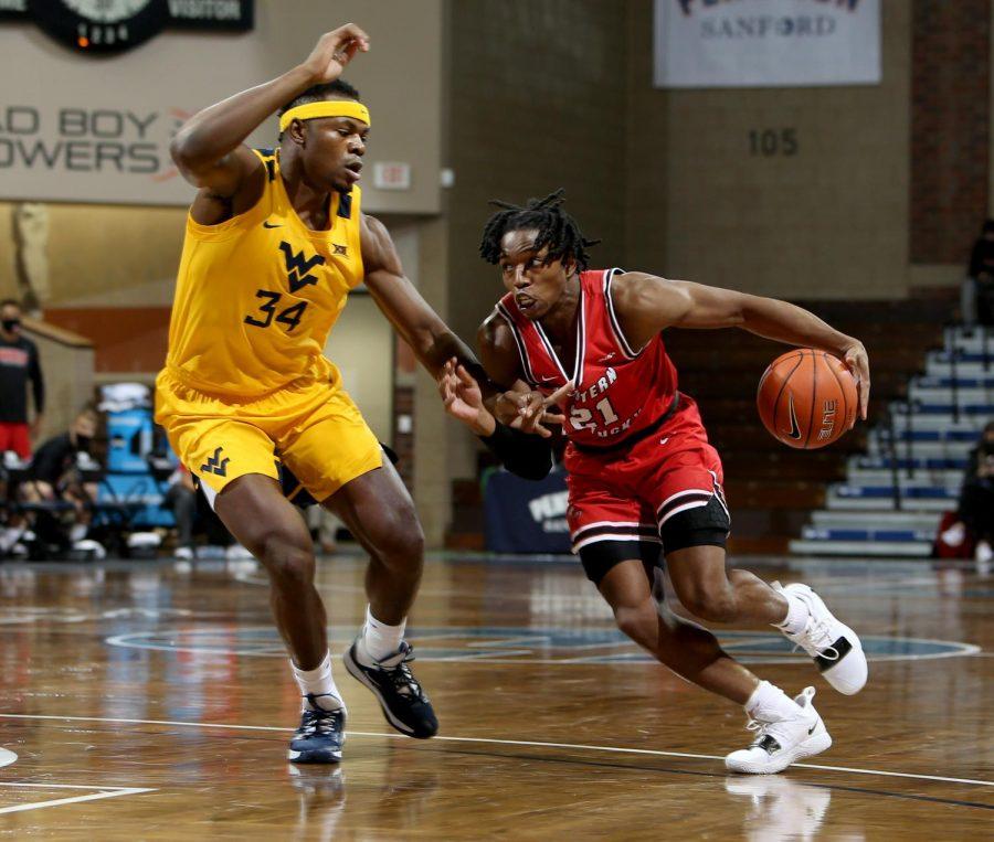 Sioux Falls, SD - Nov. 27: Kenny Cooper #21 of the Western Kentucky Hilltoppers drives to the basket against Oscar Tshiebwe #34 of the West Virginia Mountaineers.