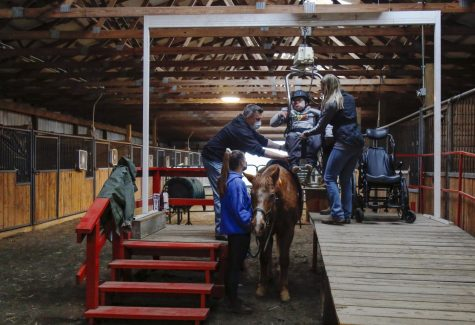 Staff members and volunteers help student rider Ben from his wheelchair to Leroy the horse before the start of a lesson. Riding lessons at New Beginnings act as both a fun activity for students as well as therapy sessions.