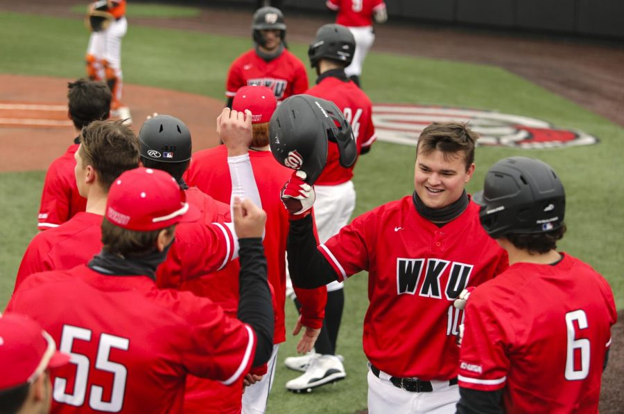 WKU infielder Davis Sims (10) is congratulated by his teammates after scoring a run during the game against the Bowling Green Falcons at Nick Denes field on March 14.
