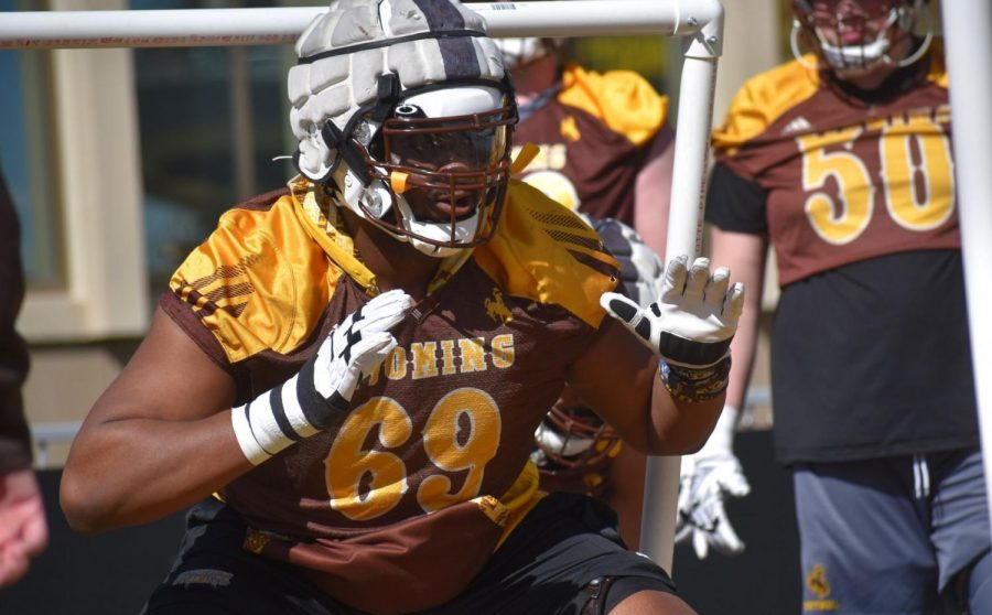 Wyoming offensive lineman Eric Abojei goes through a drill during spring practice Thursday at War Memorial Stadium in Laramie. The Cowboys' junior guard has lost approximately 50 pounds during the offseason.