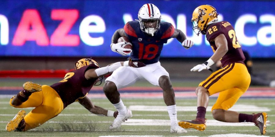 Arizona wide receiver Ma'jon Wright (18) gets hemmed in by Arizona State defensive back Kejuan Markham (12), left, and linebacker Caleb McCullough (22) in the second quarter of at Arizona Stadium on Dec. 11, 2020.