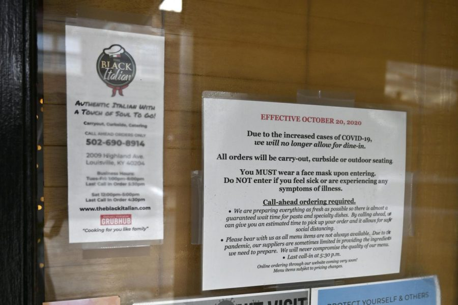 Signs on the door of The Black Italian restaurant and catering service showing the COVID-19 restrictions, in Louisville, Ky., Thursday, Dec. 3, 2020.