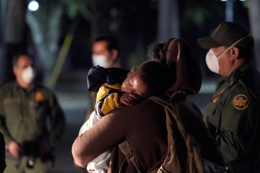 A migrant child sleeps on the shoulder of a woman at an intake area after turning themselves in upon crossing the U.S.-Mexico border, early Wednesday, March 24, 2021, in Roma, Texas. A surge of migrants on the Southwest border has the Biden administration on the defensive. The head of Homeland Security acknowledged the severity of the problem but insisted it's under control and said he won't revive a Trump-era practice of immediately expelling teens and children.