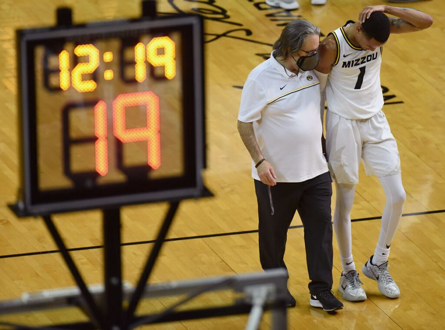 Missouri's head athletic trainer Pat Beckmann, left, walks with Xavier Pinson to join the team in a game against LSU on March 6 at Mizzou Arena in Columbia. Pinson, who entered the transfer portal in the offseason, committed via his Instagram to play for LSU next season.
