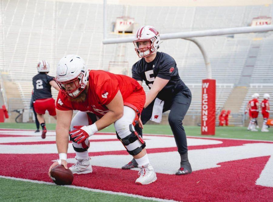 Badgers sophomore quarterback Graham Mertz takes a snap from senior center Kayden Lyles.