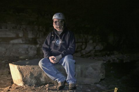 WKU Geology and Geography Professor Dr. Chris Groves sits in Crumps Cave, where he and other colleagues researched hydrology, ecology, archeology, geology and biology in 2015. The biological focus of their research was white nose syndrome – a disease threatening the lives of the federally endangered gray bats – which was discovered in Crumps Cave.