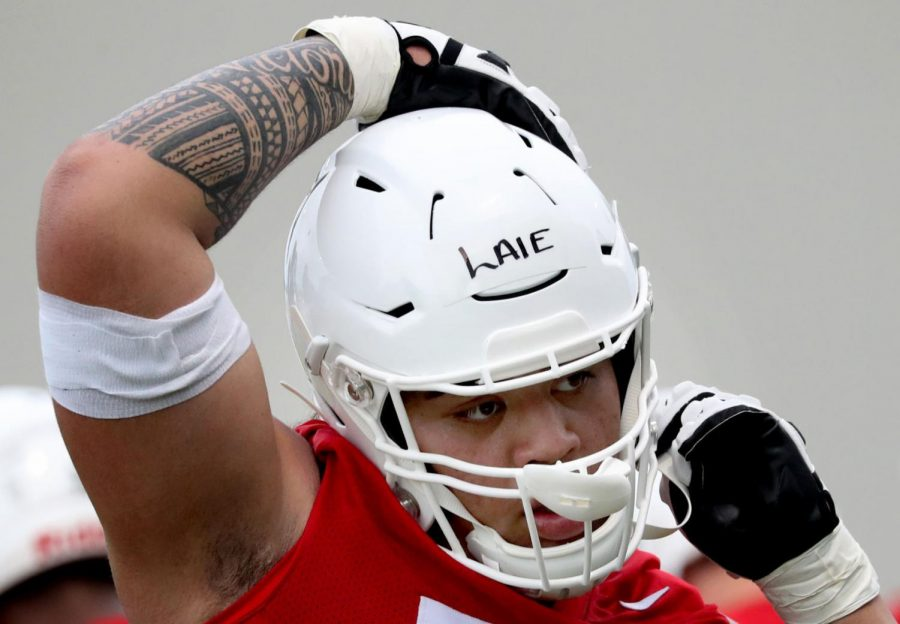 Arizona offensive lineman Donovan Laie snaps on his helmet as he gets ready to run through a blocking drill on the second day of practice for the upcoming season, Tucson, Ariz., July 26, 2019.