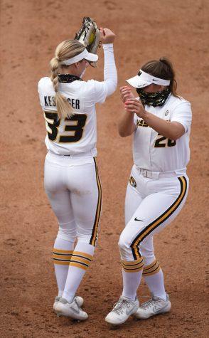 Outfielder Cayla Kessinger hip bumps Alexis Burks