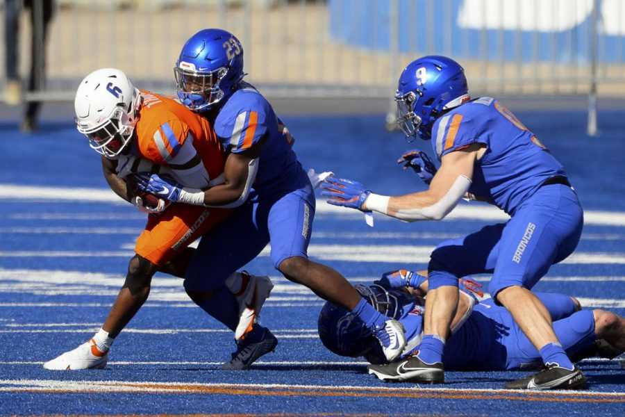 Boise State safety Seyi Oladipo (23) brings down wide receiver CT Thomas (6) during the spring football game at Albertsons Stadium on Saturday.