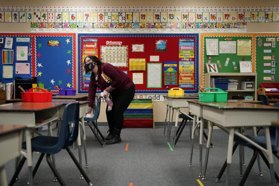 Tia+Baker+cleans+a+desk+in+a+classroom+during+a+media+tour+at+Dorothy+Eisenberg+Elementary+School%2C+Thursday%2C+Feb.+25%2C+2021%2C+in+Las+Vegas.+Pre-K+to+third+graders+started+a+two-days-per-week+%22hybrid%22+in-person+schedule+in+the+Clark+County+School+District.+Other+grades+will+be+phased+in+before+April+6.%C2%A0