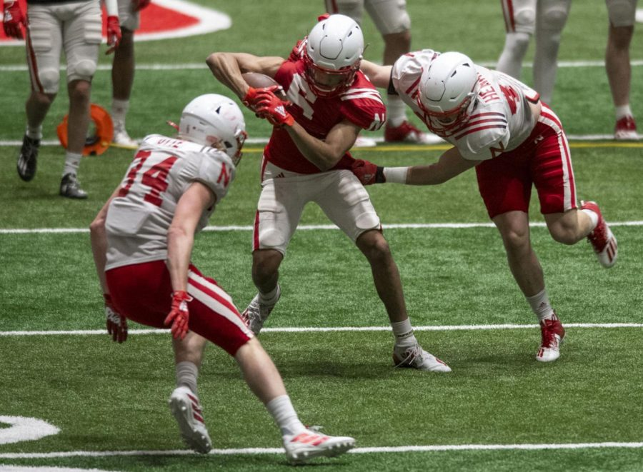 Nebraska wide receiver Samori Toure (center) tries to avoid a tackle after catching a passduring a spring football practice Wednesday at Hawks Championship Center.