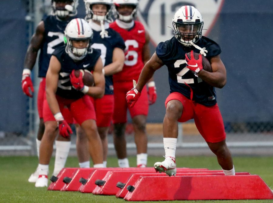 Running back Jalen John high steps his way through a drill with the other ball carriers on the first day of spring practice for the University of Arizona, Tucson, Ariz., March 23, 2021.