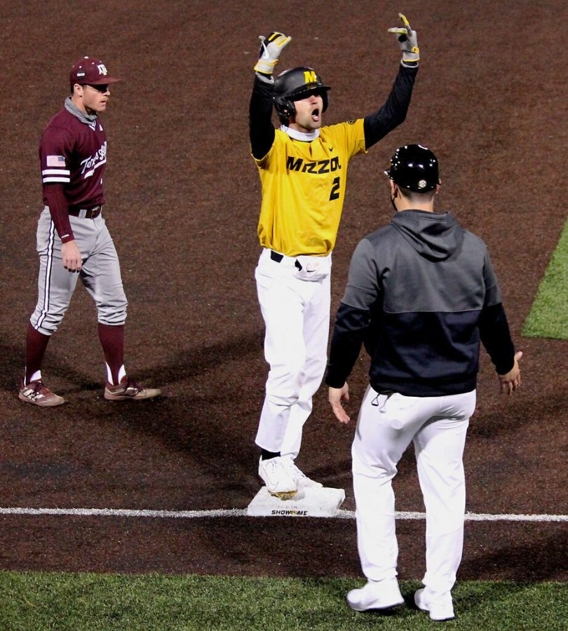 Having made it to third base, after a sprint from the second, Missouri junior Mike Coletta throws his hands up in the air