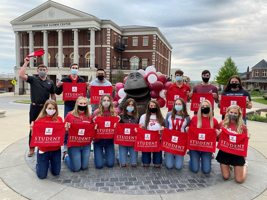 All 14 of the new student ambassadors holding their red towels next to the Big Red statute across from the Augenstein Alumni Center.