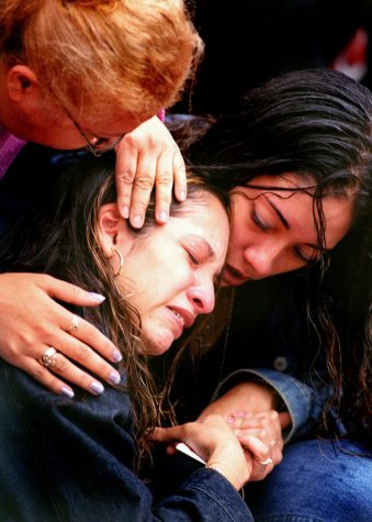 An unidentified women cries as she is consoled by her friend and a stranger in Union Square on Sept. 14, 2001 during a memorial for the people lost in the World Trade Center attacks in New York City. (Jeremy Lyverse/Western kentucky University)