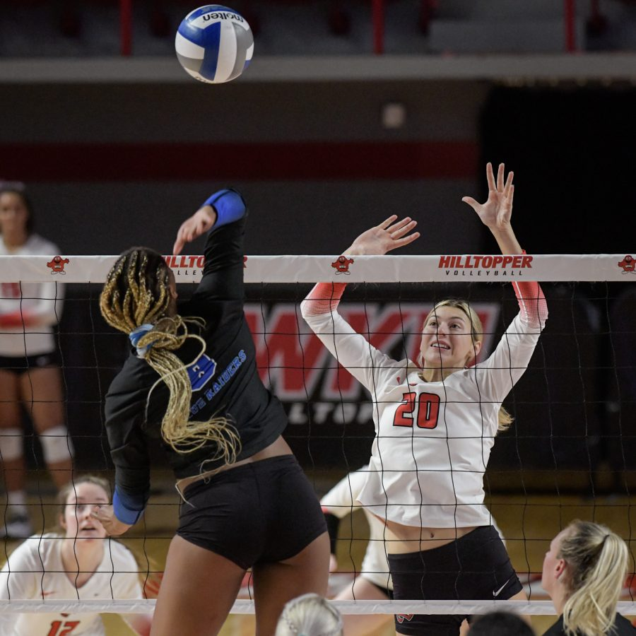 WKU Hilltoppers senior middle hitter Katie Isenbarger (20) leaps for a block against MTSU Blue Raiders redshirt sophomore middle blocker Dasia Smith (8) Friday evening, Oct. 15 of 2021 during a match WKU won 3-0 in Diddle Arena.