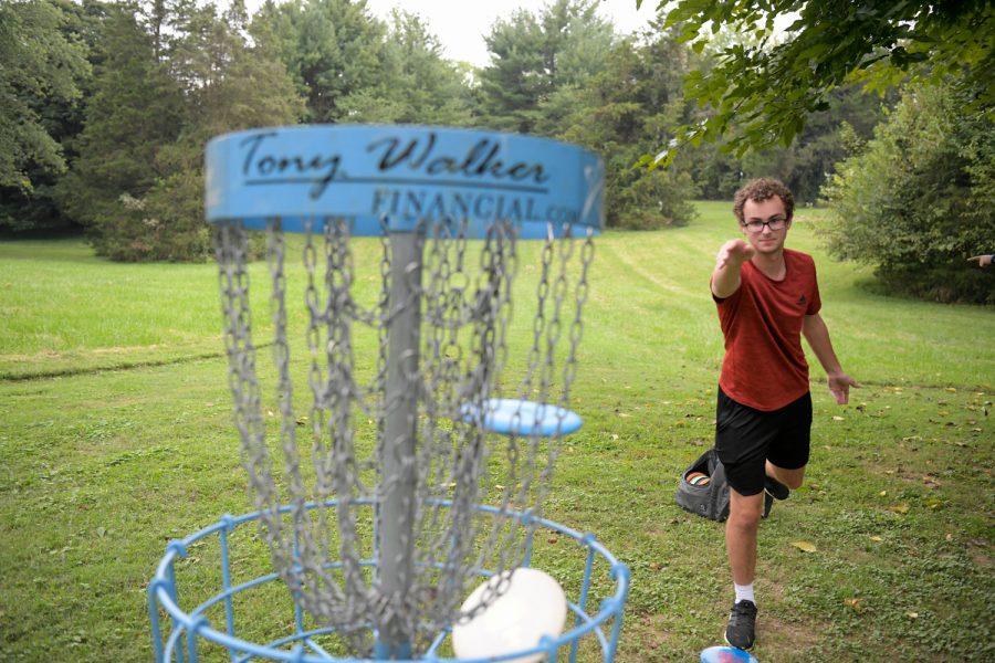 Luke Jasper, WKU Disc Golf Club member, makes a short putt while playing the course at Kereiakes Park.